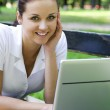 Woman using laptop on bench outdoors — Stock Photo