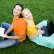 Students sitting back to back on grass — Foto Stock