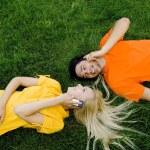 paar auf dem Gras liegend mit Handys — Stockfoto