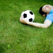 Young man lying on the grass with soccer ball — Stock Photo