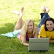 Couple using laptop outdoors — Stock Photo