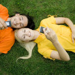Couple lying on the grass with mobile phones — Stockfoto