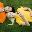 Couple lying on the grass with mobile phones — Stock fotografie