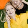 Stock Photo: Couple lying on grass with mobile phones