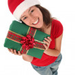 Young woman wearing a santa hat, holding a gift — Stock Photo