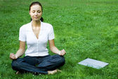 Meditating woman with laptop — Stock Photo