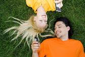 Pár ležící na trávě s mobilními telefony — Stock fotografie