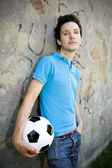 Young man holding soccer ball — Stock Photo
