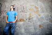 Man leaning against wall with graffiti — Stock Photo