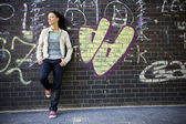 Woman leaning against brick wall with graffiti — Stock Photo
