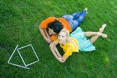 彼らの前にモデルの家の芝生に寝ころんでカップル — ストック写真