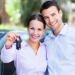 图库照片: Young couple with keys to new car