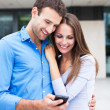 Foto de Stock  : Smiling couple with mobile phone
