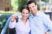 新しい車にキーと若いカップル — ストック写真