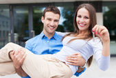 Man carrying woman into new house — Stock Photo