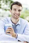 Young man outdoors with coffee — Stok fotoğraf