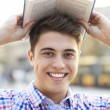 Young man with book over his head — Stock Photo