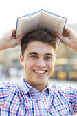 Young man with book over his head — Stok fotoğraf
