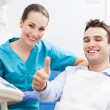 Man giving thumbs up at dentist office — Stock Photo