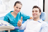 Man giving thumbs up at dentist office — ストック写真