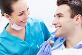 Female dentist with male patient — Stock Photo