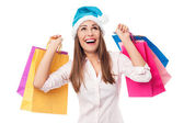 Woman wearing Santa hat holding shopping bags — Stok fotoğraf