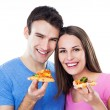 Young couple eating pizza — Stock fotografie