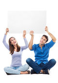 Couple holding sign above their heads — Stock Photo
