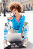 Woman sitting on skateboard with laptop — Stock fotografie
