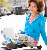 Woman sitting on skateboard with laptop — Stock Photo