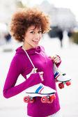 Woman holding roller-skates — Stock Photo