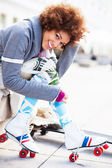 Woman putting on roller skates — Stock Photo