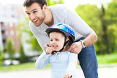 Father helping daughter with helmet — Stock Photo