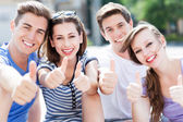 Young people with thumbs up — Stock Photo