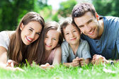 Family outdoors lying on grass — Stock Photo