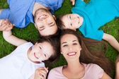 Young family lying on grass — Stock Photo