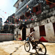 A young Boy Riding his bike in the old streets of Stonecity under the red, blue and white flags — Stock Photo