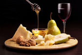 Parmesan cheese, pears, honey, walnuts and wineglass — Stock Photo