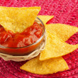 Bowl of hot sauce with nachos on red placemat — Stock Photo