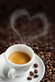 Coffee cup with heart- shaped steam on background of coffee beans — Stock Photo