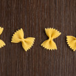 Four bow tie pasta on wooden background — Stock Photo