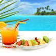 Summer cocktail and fruit skewers on exotic seascape — Stock Photo #26888399