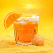Foto Stock: Summer cocktail and scallop shell on beach at sunset