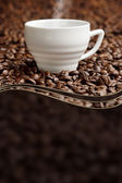 Steaming cup on background of coffee beans with copy space — Stock Photo