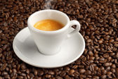 Steaming cup of coffee on background of coffee beans — Stock Photo