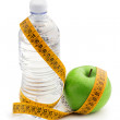 Green apple, bottle of water and tape measure — Stock Photo