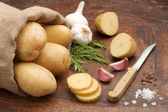 Jute bag of raw potatoes, seasonings and potatoes cut — Stock Photo