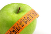 Green apple wrapped by a measuring tape — Stock Photo