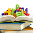 Stack of books with colorful plastic letters on top — Stock Photo