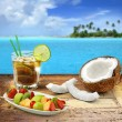 Cuba libre and tropical fruit on a wooden table in a polynesian seascape — Stock Photo #34739721